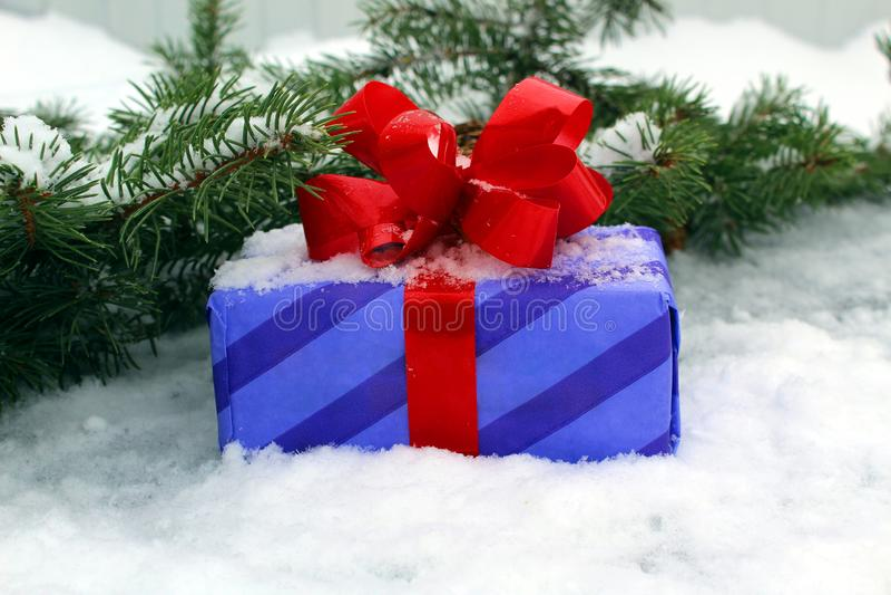De gift van het nieuwjaar met een rode boog op de achtergrond van de Kerstboom en de sneeuw stock afbeeldingen