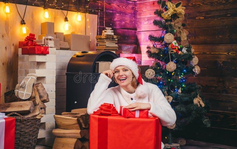 De gift van het nieuwjaar Het nieuwe meisje van de jaarvooravond Uitdrukkingengezicht De kerstboom verfraait thuis Het glimlachen stock fotografie