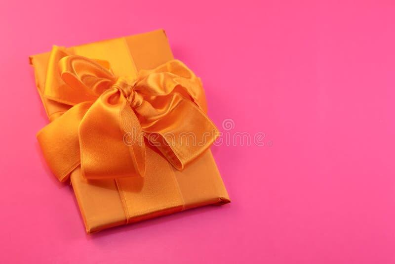 De gift wordt ingepakt en met een gele boog op een roze achtergrond met exemplaarruimte verfraaid Vlak leg, hoogste mening De rui royalty-vrije stock afbeeldingen