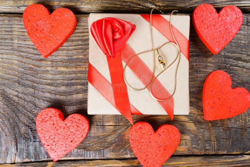 De gift wordt ingepakt in Kraftpapier-document en met een rood lint met roze gebonden die een tegenhanger in de vorm van belemmer royalty-vrije stock afbeelding