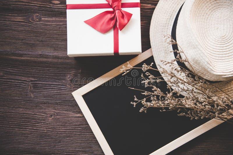 De giftdoos met decoratieve decoratie, de bloemen en de hoed op het bord schepen in Oude houten achtergrond, exemplaarruimte royalty-vrije stock fotografie