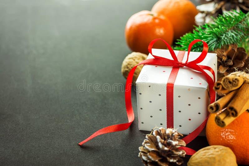 De giftdoos van Kerstmisnieuwjaren met rode lintboog De takken van de de okkernotenspar van mandarijnendenneappels De kaartmalpla stock afbeelding