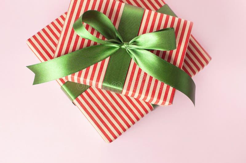 De giftdozen met groen lint op roze achtergrond hoogste meningsvlakte lagen Het vakantieconcept, nieuw jaar of de doos van de Ker royalty-vrije stock fotografie