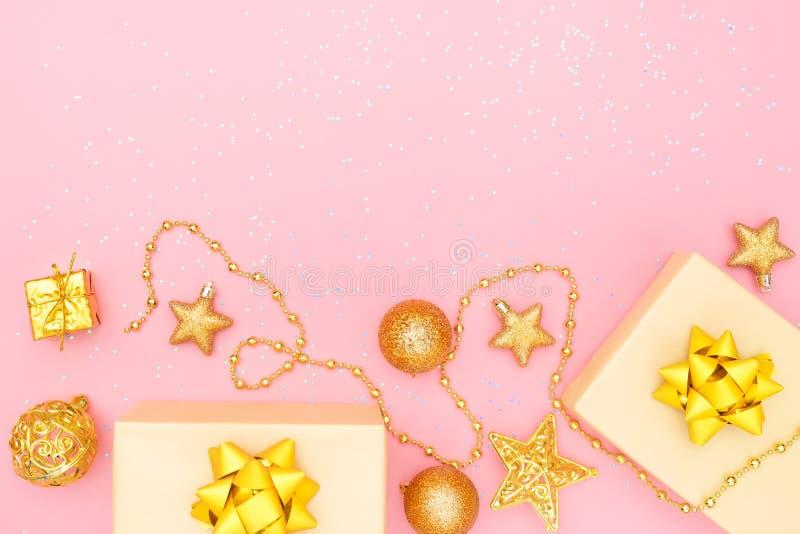 De giftendozen of stelt dozen met gouden bogen, ster en bal op roze achtergrond voor verjaardag, Kerstmis of huwelijksceremonie v stock afbeeldingen