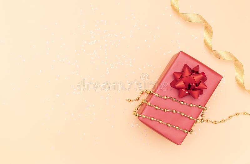 De giftendozen of stelt dozen met rode bogen, ster en bal op gouden achtergrond voor verjaardag, Kerstmis of huwelijksceremonie v stock foto