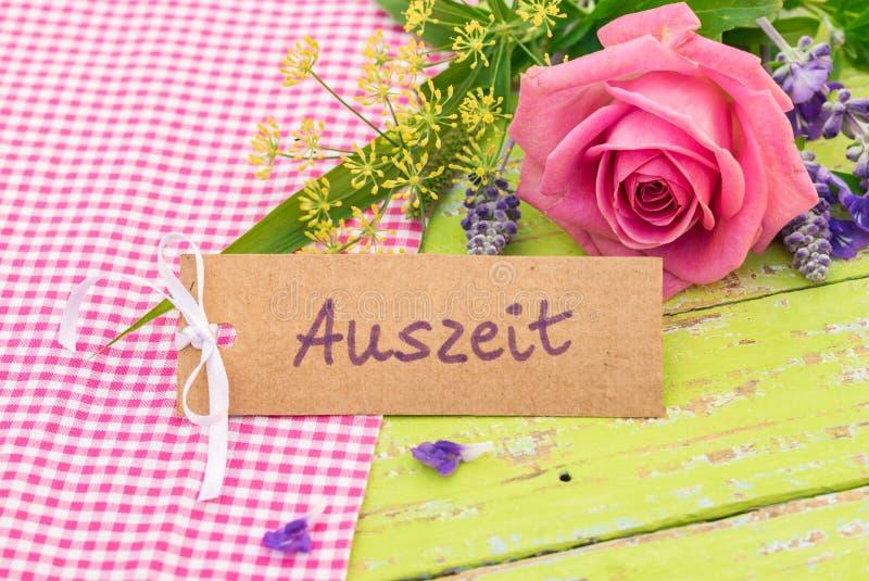 De giftkaart met Duits woord, Auszeit, betekent onderbreking met boeket van bloemen royalty-vrije stock foto