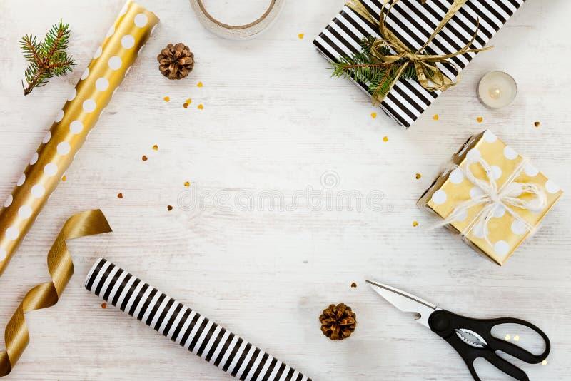 De giftvakjes verpakten in zwart-witte gestreept en goden gestippeld document met, pijnboom, kegels, kaars en verpakkingsmaterial royalty-vrije stock foto