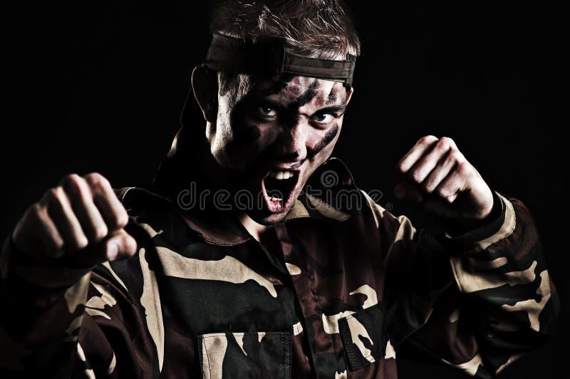 De gillende militair wil met vijand vechten stock foto