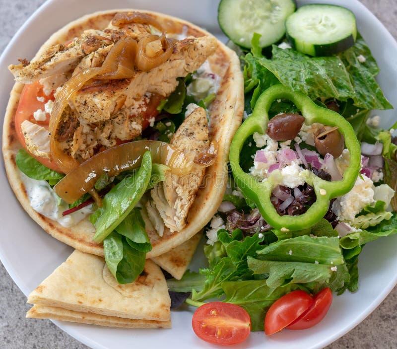 De giro van het kippenpitabroodje en Griekse salade Het gezonde eten mages stock foto