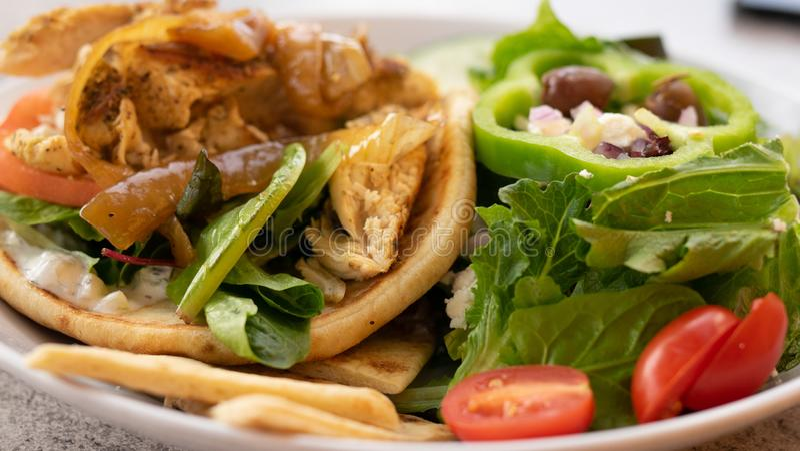De giro van het kippenpitabroodje en Griekse salade Het gezonde eten mages royalty-vrije stock afbeeldingen