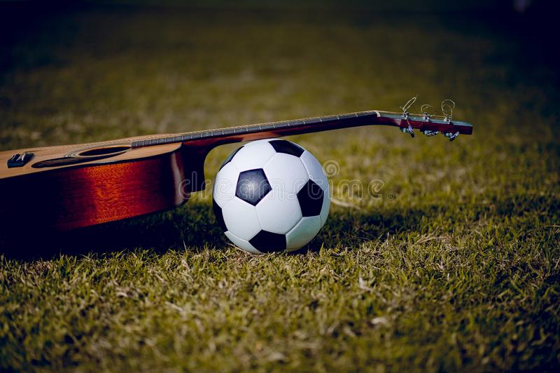 De gitaar en de voetbal worden geplaatst in groene gazons Muziek en sporten royalty-vrije stock foto's