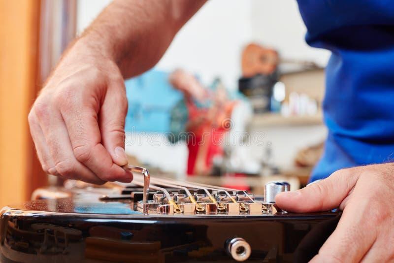 De gitaarmaker past elektrische gitaar aan stock afbeelding