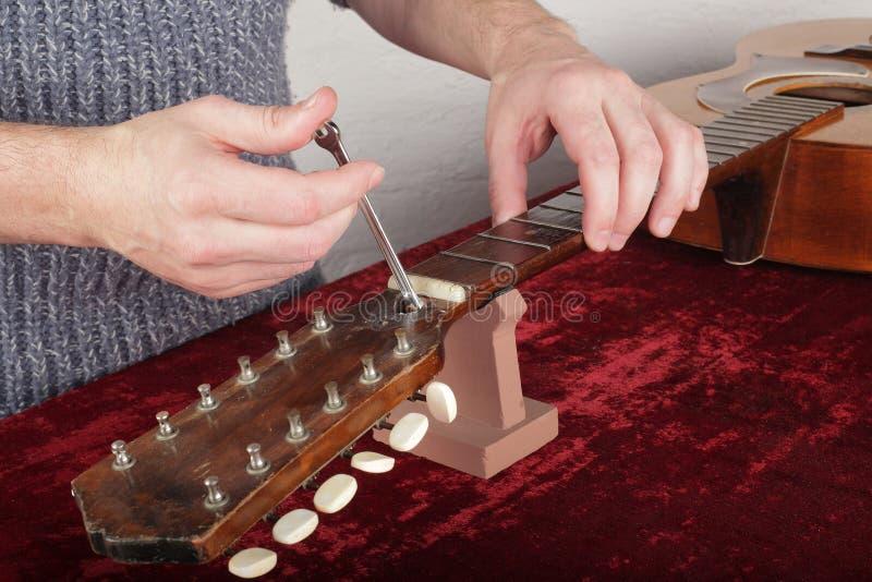 De gitaarreparatie en dienst - de Arbeider maakt aanpassing van een tru op stock foto's
