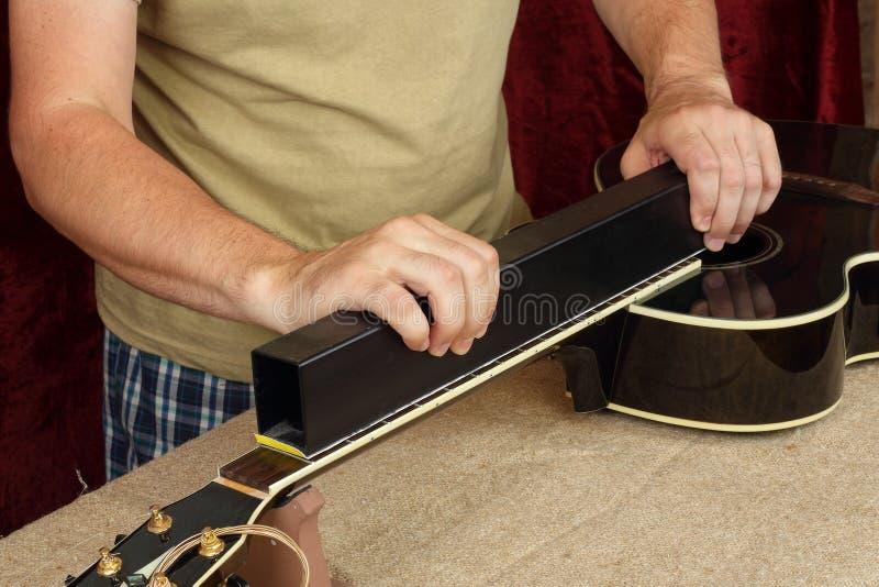 De gitaarreparatie en dienst - lijstwerk van de de gitaarhals van Arbeidersmalen het zwarte royalty-vrije stock afbeeldingen