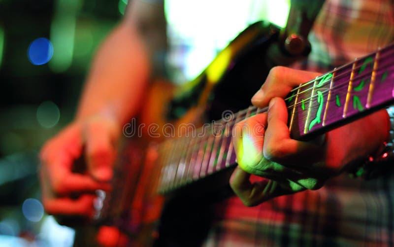 De gitarist overhandigt het spelen gitaar stock afbeeldingen