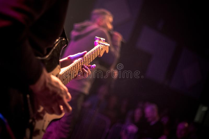 De gitarist speelt een elektrische gitaar op stadium met lichten op de achtergrond Sluit omhoog stock fotografie