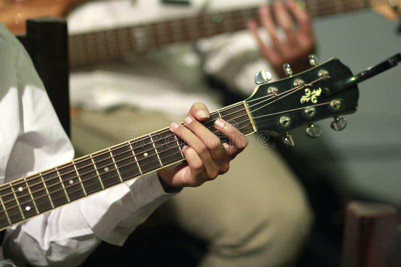 De gitaristen spelen gitaarsnaarinstrumenten royalty-vrije stock foto
