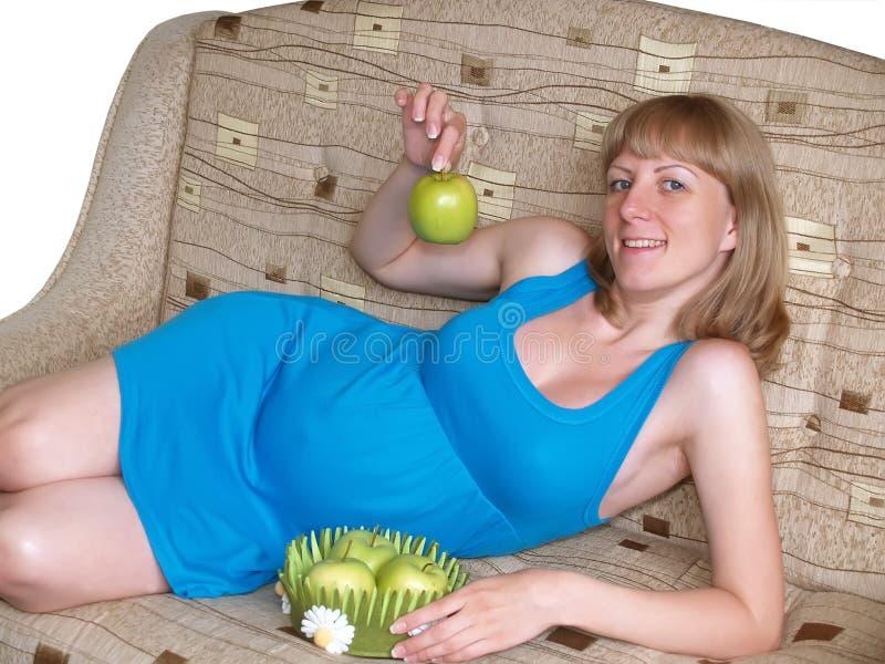 De glade gravid kvinnahållna gör grön äpplet som ligger på en soffa arkivfoton
