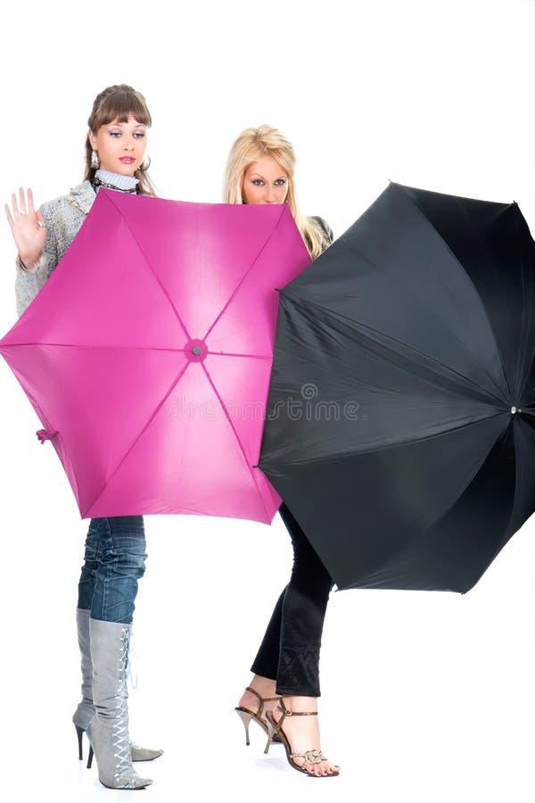 De gladlynt kvinnorna med ett rosa och svart paraply arkivbilder