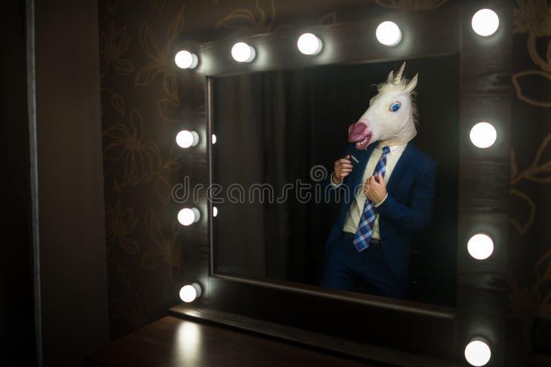 De glamourkerel in elegant kostuum en komisch masker bekijkt zich in de spiegel stock afbeelding