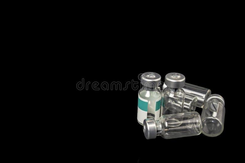 De glasfles van het vaccin ligt op zwarte dichte omhooggaand als achtergrond stock foto