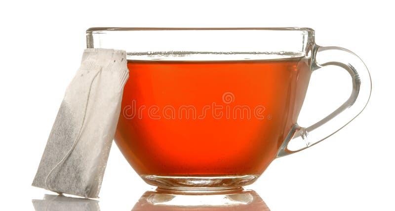 De glaskop met thee en theezakje dichte omhooggaand op wit isoleerde achtergrond stock afbeeldingen