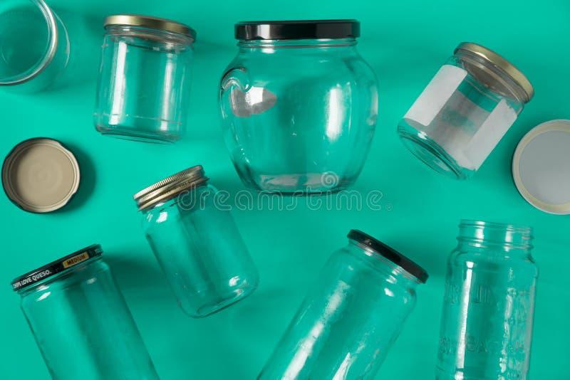 De glaskruiken met deksels, wintertalings groene achtergrond, hoogste meningsvlakte leggen recyclingsconcept royalty-vrije stock afbeeldingen