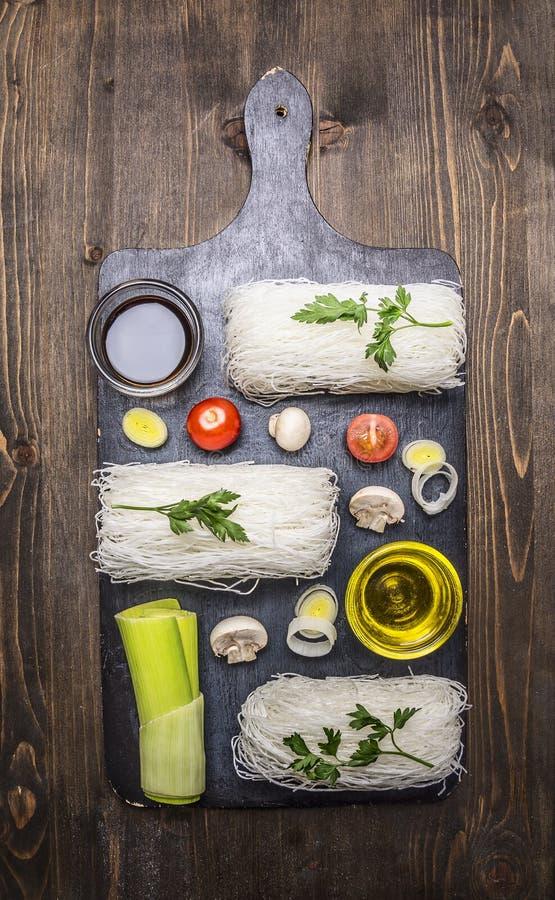 De glasnoedels met groenten en de kruiden op een knipsel schepen het koken en vegetarisch concept op houten hoogste mening in rus stock afbeelding