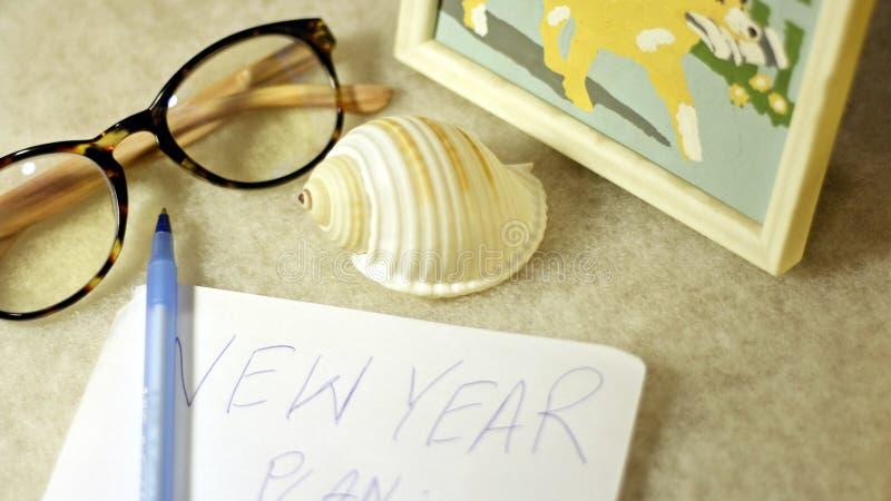 De glazen, kammossel, stellen een pen en een stuk van document met handschrift voor - samenstelling op een lichte achtergrond royalty-vrije stock fotografie