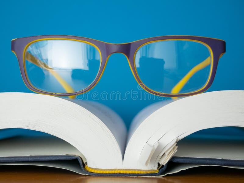 De glazen leggen bovenop geopend boek royalty-vrije stock afbeelding