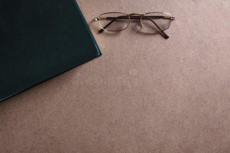 De glazen liggen dichtbij het groene boek op de houten achtergrond Het concept lezing en onderwijs Hoogste mening, exemplaarruimt stock fotografie