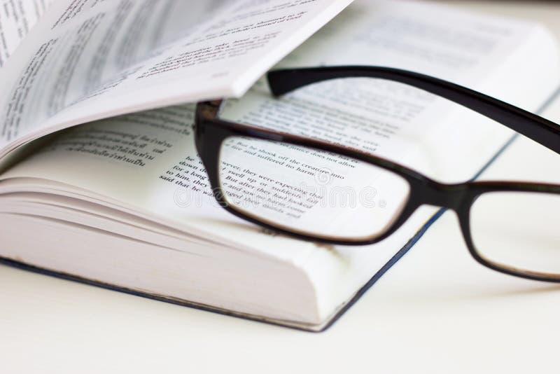 De glazen op het boek aan referentie de pagina royalty-vrije stock afbeelding