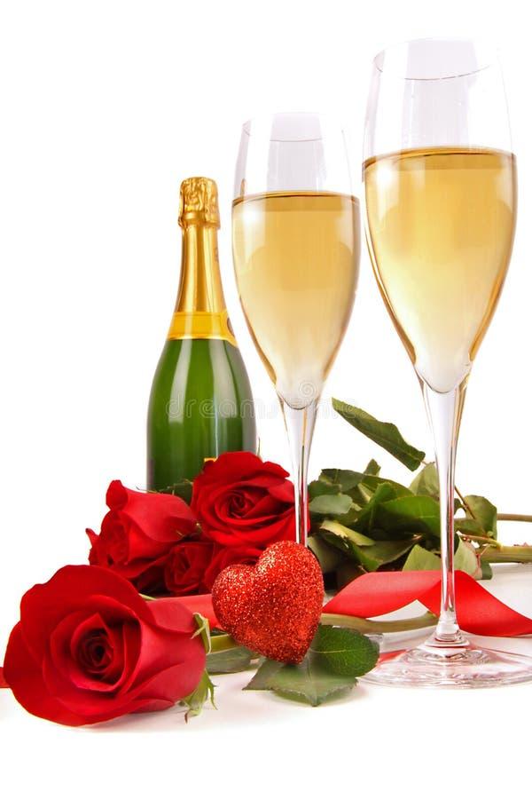 De glazen van Champagne met rode rozen en weinig hart stock afbeelding