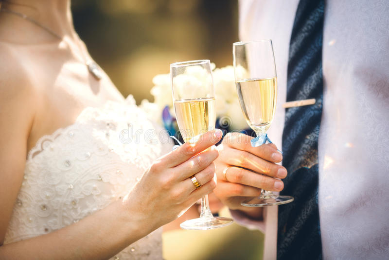 De glazen van de de holdingswijn van het huwelijkspaar stock afbeeldingen