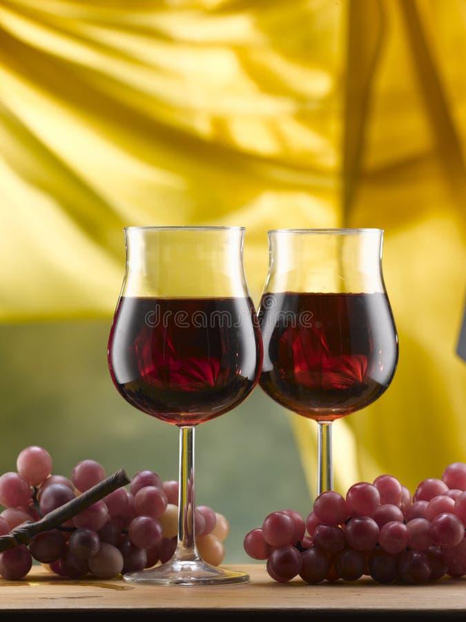 De glazen van de rode die wijnstam met druiven worden gediend stock foto's