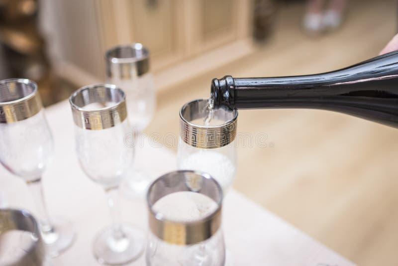De glazen worden gevuld met champagne van de fles stock afbeelding