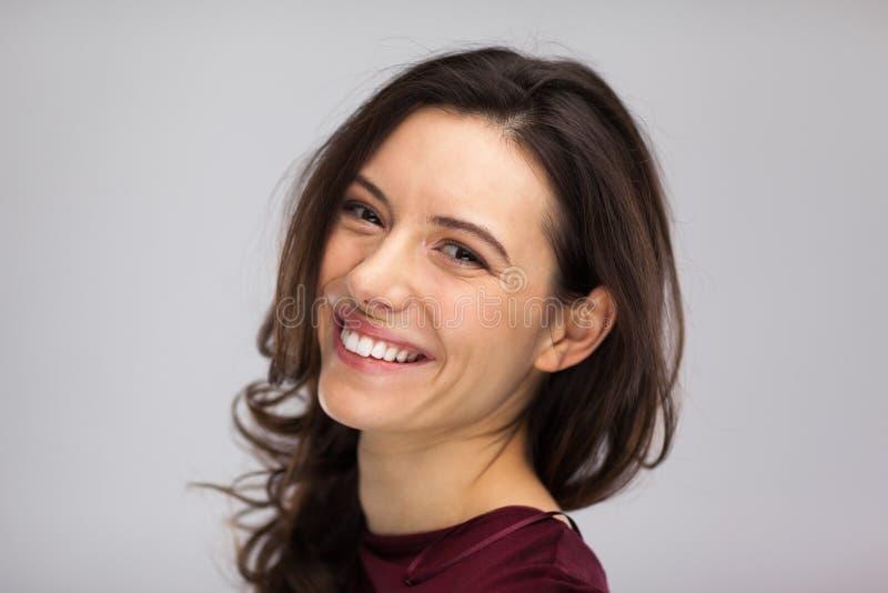 De glimlach van het vrouwengezicht, sluit omhoog grijze achtergrond stock afbeeldingen