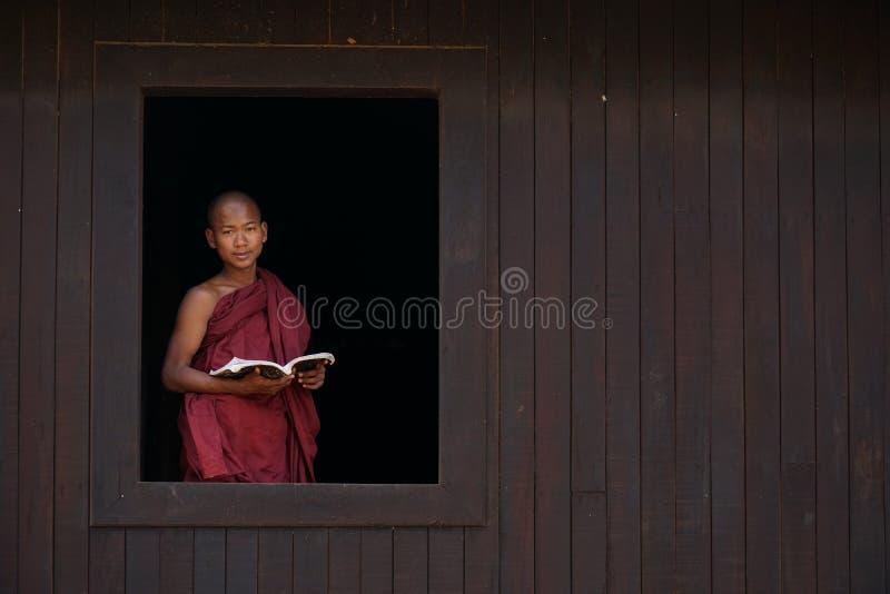 De glimlachen van de beginnermonnik bij het oude tempelvenster stock foto