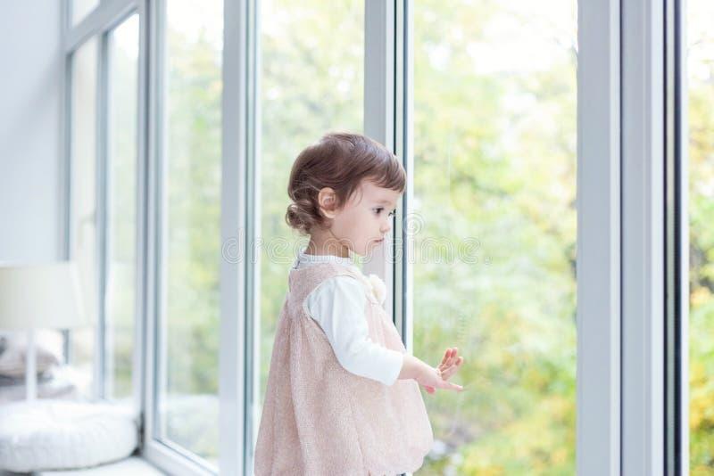 De glimlachen van het babymeisje in een ruimte dichtbij het venster stock afbeelding