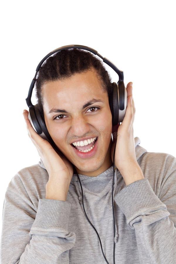De glimlachende Amerikaanse mannelijke tiener luistert aan muziek stock fotografie