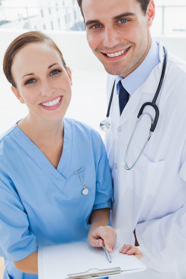 De glimlachende arts en de chirurg die terwijl het houden documenteren togeth stellen stock foto's