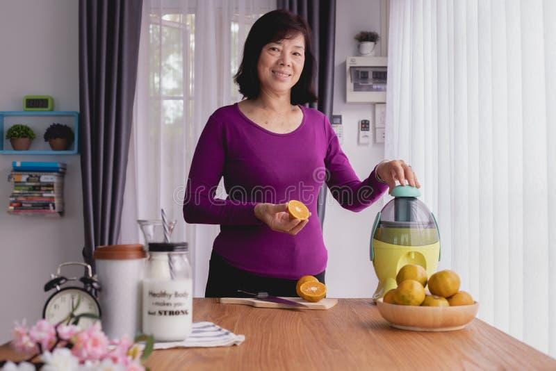 De glimlachende Aziatische bejaarden maken jus d'orange door mixer stock fotografie