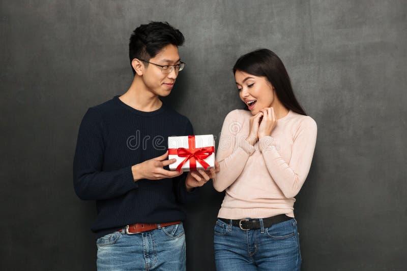 De glimlachende Aziatische mens in oogglazen stelt gift aan verrast meisje voor stock foto's