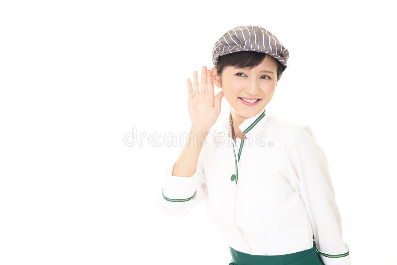 De glimlachende Aziatische serveerster luistert zorgvuldig stock afbeelding