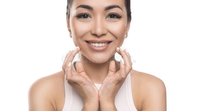 De glimlachende Aziatische vrouw wat betreft hier ziet door handen en het bekijken camera onder ogen Ge?soleerdj op witte achterg stock foto