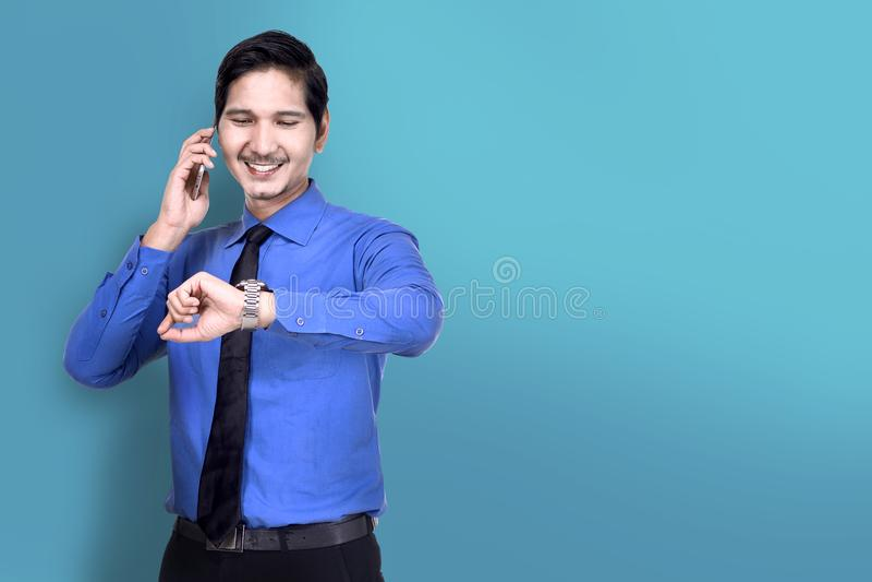 De glimlachende Aziatische zakenman controleert het horloge terwijl het spreken op telefoon royalty-vrije stock afbeeldingen