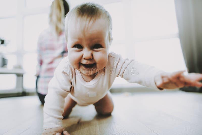 De glimlachende Baby kruipt en de Moeder zit dichtbij Venster royalty-vrije stock foto's