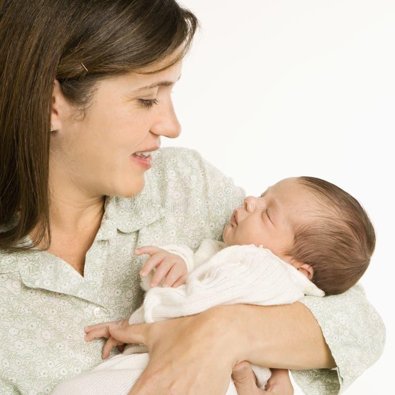 De glimlachende baby van de moederholding. stock afbeeldingen