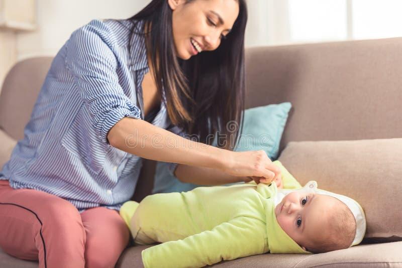 de glimlachende baby van de moeder kledende zuigeling omhoog royalty-vrije stock afbeelding