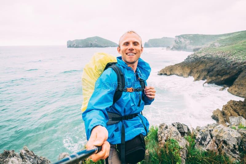 De glimlachende backpakcer reiziger neemt selfie foto op oceaankust stock foto